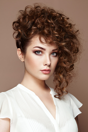 Photo pour Brunette woman with curly and shiny hair. Beautiful model with wavy hairstyle. Fashion photo - image libre de droit