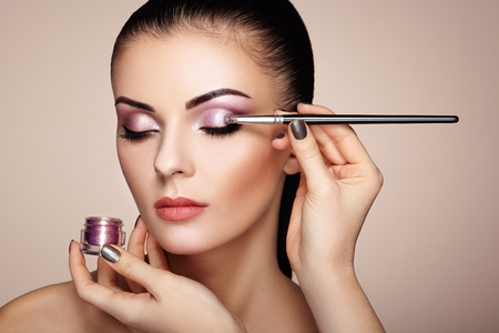 Photo pour Makeup artist applies eye shadow. Beautiful woman face. Perfect makeup. Makeup detail. Beauty girl with perfect skin. Nails and manicure - image libre de droit