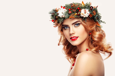 Foto de Portrait of beautiful young woman with Christmas wreath. Beautiful New Year and Christmas tree holiday hairstyle and makeup. Beauty girl portrait isolated on white background. Colorful makeup and hair - Imagen libre de derechos