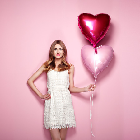 Foto de Beautiful young woman with heart shape air balloon on color background. Woman on Valentine's Day. Symbol of love - Imagen libre de derechos
