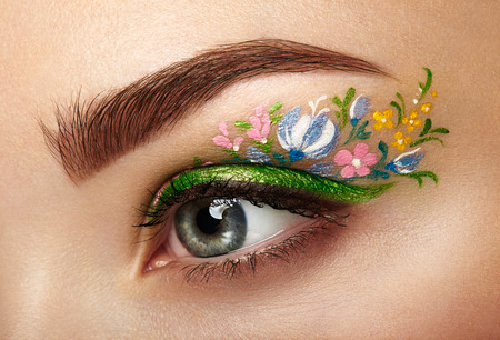 Eye makeup girl with a flowers. Spring makeup. Beauty fashion. Eyelashes. Cosmetic Eyeshadow. Make-up detail. Creative woman holiday make-up