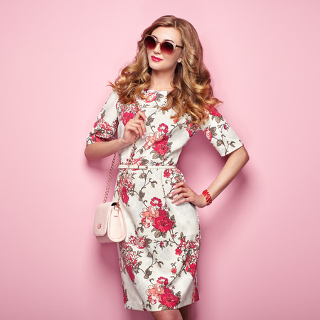 Photo for Blonde young woman in floral spring summer dress. Girl posing on a pink background. Summer floral outfit. Stylish wavy hairstyle. Fashion photo. Glamour lady in sunglasses with handbag - Royalty Free Image