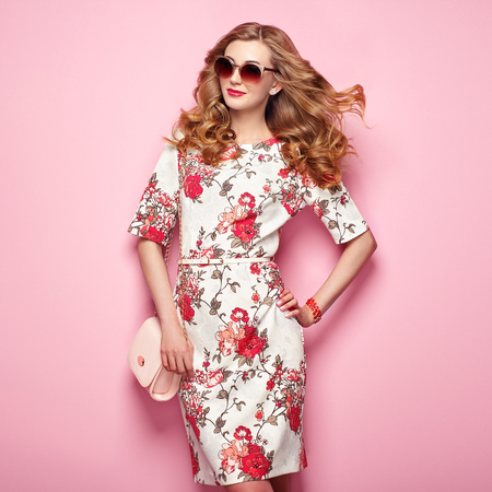 Photo pour Blonde young woman in floral spring summer dress. Girl posing on a pink background. Summer floral outfit. Stylish wavy hairstyle. Fashion photo. Glamour lady in sunglasses with handbag - image libre de droit