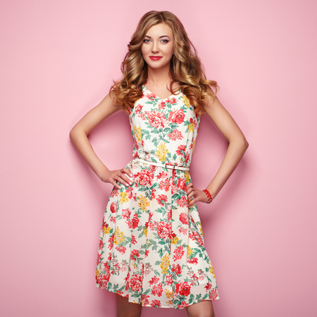 Photo pour Blonde young woman in floral spring summer dress. Girl posing on a pink background. Summer floral outfit. Stylish wavy hairstyle. Fashion photo. Blonde lady - image libre de droit