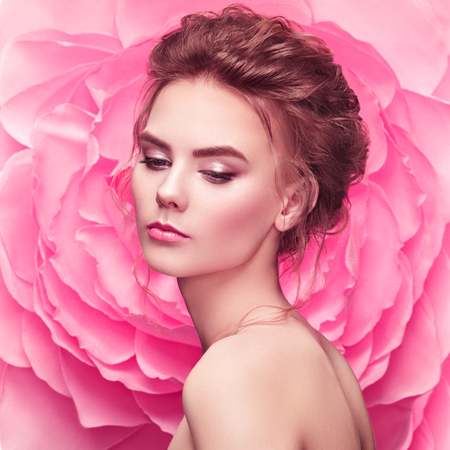 Foto de Beautiful woman on the background of a large flower. Beauty summer model girl with pink peony. Young woman with elegant hairstyle and makeup. Fashion photo - Imagen libre de derechos