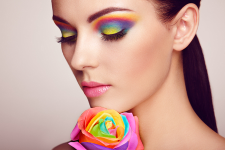 Photo pour Portrait of beautiful young woman with rainbow rose. Bright colors. Long eyelashes, vivid colorful eyeshadows. Rainbow make up. Multicolored flowers - image libre de droit