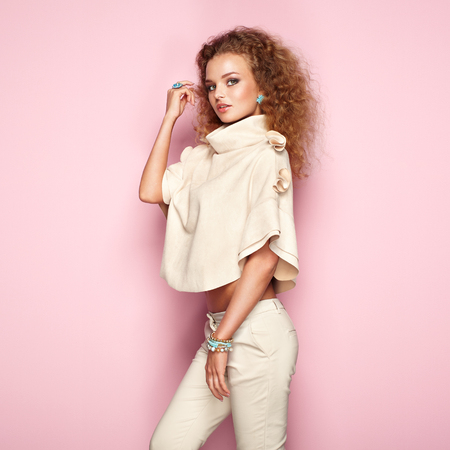 Foto de Fashion portrait of woman in summer outfit. Girl posing on pink background. Stylish curly hairstyle. Glamour lady - Imagen libre de derechos