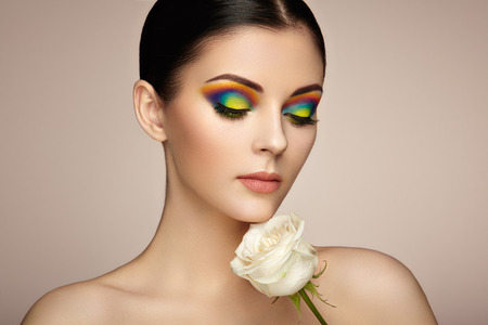 Photo pour Portrait of beautiful young woman with rainbow make-up. Girl summer. Long eyelashes, vivid colorful eyeshadows. White rose. Multicolored - image libre de droit