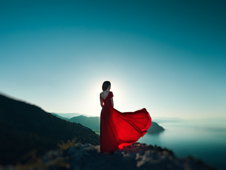 Foto de Young beautiful woman in red dress looking to mountains sea. Girl on the nature on blue sky background. Fashion photo - Imagen libre de derechos