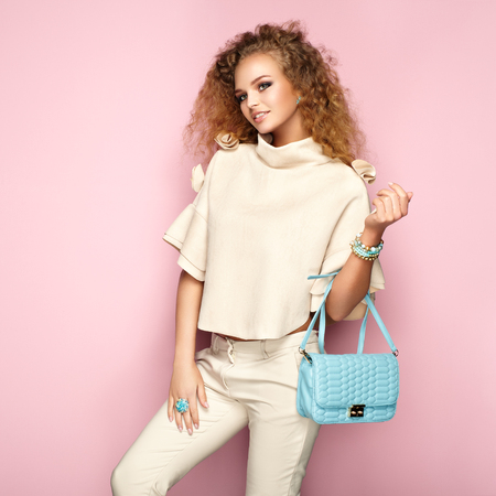 Photo pour Fashion portrait of woman in summer outfit. Girl posing on pink background. Blue handbag. Stylish curly hairstyle. Glamour lady - image libre de droit