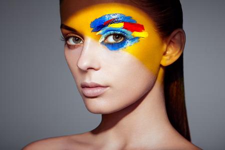 Photo pour Fashion model woman with colored face painted. Beauty fashion art portrait of beautiful woman with colorful abstract makeup. Face painted paints. Multicolor design - image libre de droit