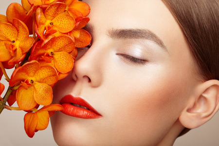 Foto de Portrait of beautiful young woman with orchid. Brunette woman with luxury makeup. Perfect skin. Eyelashes. Cosmetic eyeshadow. Orange flowers - Imagen libre de derechos