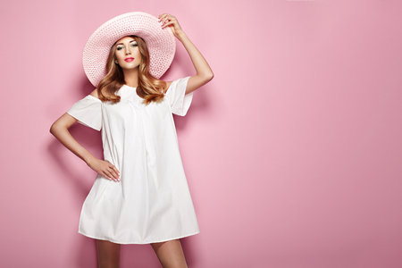 Photo pour Blonde Young Woman in elegant white Dress and Summer Hat. Girl posing on a Pink Background. Jewelry and Clothing. Fashion photo - image libre de droit