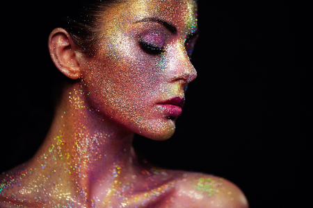 Foto de Portrait of Beautiful Woman with Sparkles on her Face. Girl with Art Make-Up in Color Light. Fashion Model with Colorful Makeup - Imagen libre de derechos