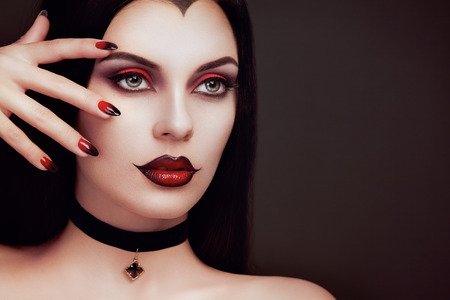 Photo pour Halloween Vampire Woman portrait. Beautiful Glamour Fashion Sexy Vampire Lady with long dark Hair, beauty make up and Costume - image libre de droit