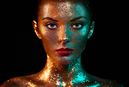 Photo pour Portrait of Beautiful Woman with Sparkles on her Face. Girl with Art Make-Up in Color Light. Fashion Model with Colorful Makeup - image libre de droit