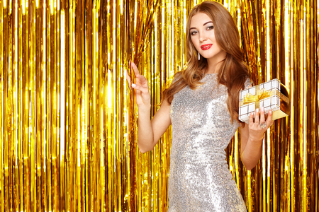 Foto de Beautiful Woman celebrating New Year and Christmas. Girl with Box of Gifts. Girl posing over Golden sparkly background. Happy New Year. Holiday and Party - Imagen libre de derechos