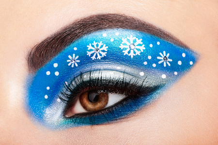 Photo pour Eye girl makeover snowflakes. Winter christmas makeup. Beauty fashion. Eyelashes. Cosmetic Eyeshadow. Makeup detail. Creative woman holiday make-up - image libre de droit
