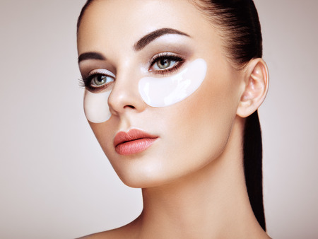 Photo pour Portrait of Beauty Woman with Eye Patches. Woman Beauty Face with Mask under Eyes. Beautiful Female with natural Makeup and White Cosmetics Collagen Patches on Fresh Facial Skin - image libre de droit