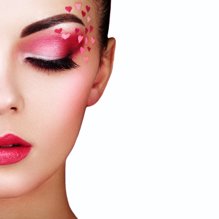 Photo pour Face of Beautiful Woman with Holiday Makeup Heart. Valentine's Day make-up. Lips in Pink Lipstick. Makeup detail. Face of girl on a White background - image libre de droit