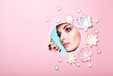 Foto de Conceptual Beauty Portrait of Beautiful Young Woman. Face of Girl with Spring Pink Make-up. Beauty Fashion Model Woman Face perfect Skin. Paper Flowers on Pink Background - Imagen libre de derechos