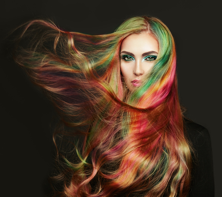 Foto de Portrait of young beautiful woman with long flowing hair. Model with perfect Healthy Dyed Hair. Rainbow Hairstyles - Imagen libre de derechos