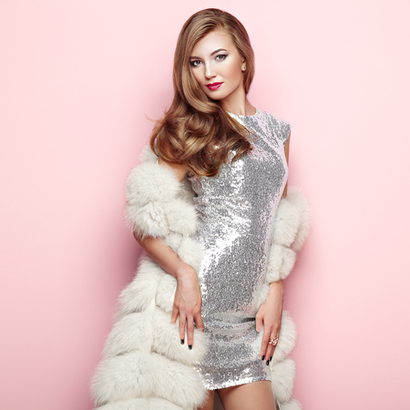 Photo for Fashion Portrait Young Woman in white Fur Coat. Girl with Elegant Hairstyle Posing on a Pink Background. Lady Posing in Eco-Fur Coat. Beautiful Luxury Winter Woman. Fashion Model in Silver Dress - Royalty Free Image