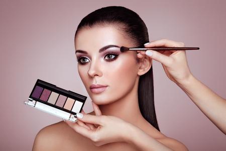 Foto de Makeup Artist applies Eye Shadow. Beautiful Woman Face. Perfect Makeup. Make-up detail. Beauty Girl with Perfect Skin. Nails and Manicure. Eye Shadow Palette - Imagen libre de derechos
