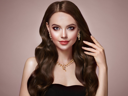 Foto de Brunette Girl with Long Healthy and Shiny Curly Hair. Care and Beauty. Beautiful Model Woman with Wavy Hairstyle. Make-Up and Jewelry - Imagen libre de derechos