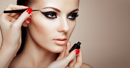 Photo for Makeup Artist Applies Eyeshadow. Beautiful Woman Make-up Eye with Black Liner. Fashion Makeup Arrows. Red Nails Perfect Skin - Royalty Free Image