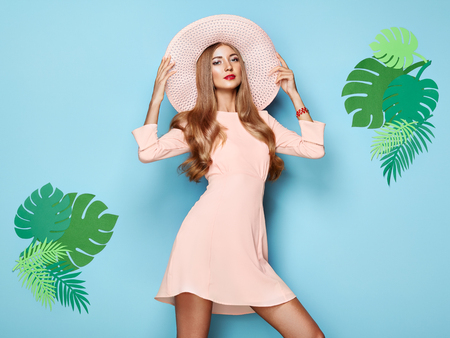 Photo pour Portrait of Fashion Young woman in Pink Dress. Lady in Stylish Summer Outfit. Girl Posing on a Blue Background. Stylish Hairstyle. Model On the background of Tropical Leaves - image libre de droit