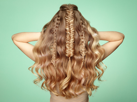 Foto de Blonde Girl with Long and Shiny Curly Hair. Beautiful Model Woman with Curly Hairstyle. Care and Beauty Hair Products. Lady with braided hair - Imagen libre de derechos