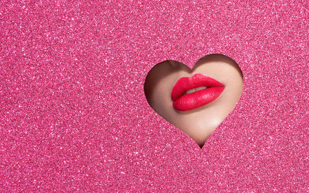 Foto de Beautiful Plump Bright Lips Of a Young Beautiful Woman with Red Lipstick Look Into the Pattern of Heart Shaped made of Colored Paper. Holiday Patterns. Valentine's Day. Beautiful Love Make-up - Imagen libre de derechos