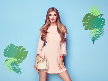 Foto de Portrait of Fashion Young woman in Pink Dress. Lady in Stylish Summer Outfit. Girl Posing on a Blue Background. Stylish Hairstyle. Model On the background of Tropical Leaves - Imagen libre de derechos