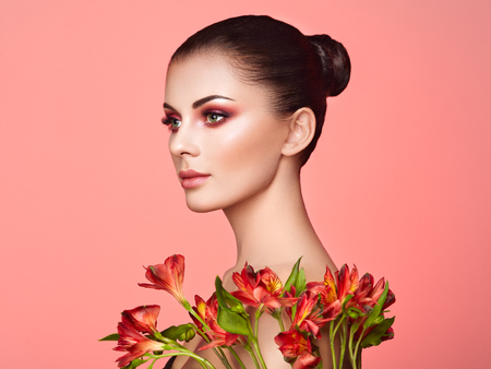 Photo pour Portrait of beautiful young woman with Alstroemeria flowers. Brunette woman with luxury makeup. Perfect skin. Eyelashes. Cosmetic eye shadow. Red flowers. Coral color - image libre de droit