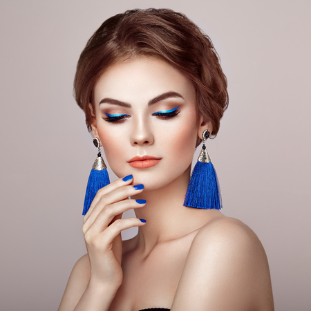 Photo pour Beautiful Woman with Large Earrings Tassels jewelry Blue color. Perfect Makeup and Elegant Hairstyle. Blue Make-up Arrows. Blue nails manicure - image libre de droit
