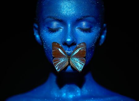 Foto de Fashion model woman in blue bright sparkles and neon lights posing in studio.  Portrait of beautiful sexy woman with blue butterfly. Art design colorful glitter glowing make up - Imagen libre de derechos
