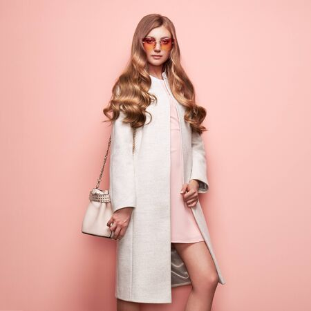 Photo for Young elegant woman in trendy white coat. Blond hair, pink dress, isolated studio shot. Fashion autumn lookbook. Model woman with handbag - Royalty Free Image