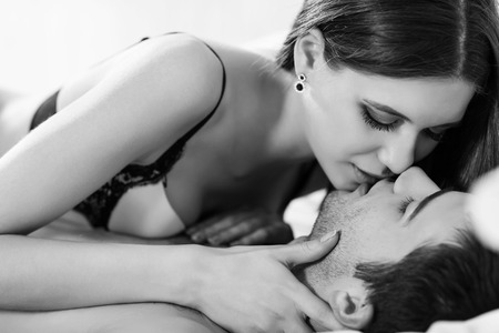 Photo for Young passionate couple making love in bed - Royalty Free Image