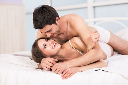 Foto de Young love couple in bed, romantic scene in bedroom - Imagen libre de derechos