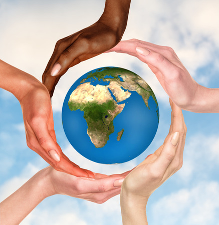 Foto de Beautiful conceptual symbol of the Earth globe with multiracial human hands around it. Unity and world peace concept. Elements of this image furnished by NASA - Imagen libre de derechos