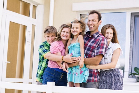 Big happy family stands beside their house