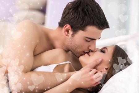 Foto de Beautiful young loving couple lying in bed and kissing - Imagen libre de derechos