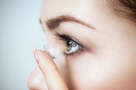 Photo pour Close-up shot of young woman wearing contact lens. - image libre de droit