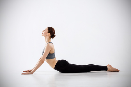 Photo pour Attractive young woman practicing yoga over gray background. - image libre de droit