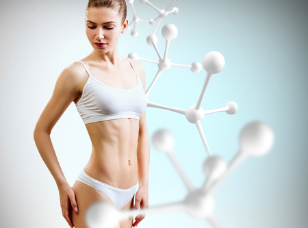 Photo for Woman with perfect body near big molecule chain. Slimming concept. - Royalty Free Image
