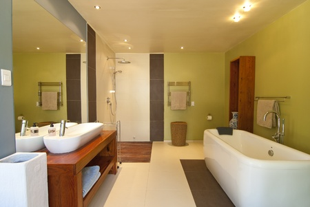 Modern bathroom with pastel coloured walls and white bath. There\'s also a wood floored open shower