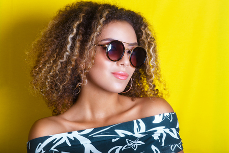 Photo for portrait indoors of a young afro american woman in sunglasses. Yellow background. Lifestyle. - Royalty Free Image