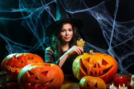 Photo pour Halloween concept - young woman with halloween sweet and candy with cheerful smiling over spider web and with curved pumpkins background. - image libre de droit