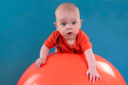 Foto für Cute baby lying on the orange fitball on the blue background. Concept of caring for the baby's health. - Lizenzfreies Bild